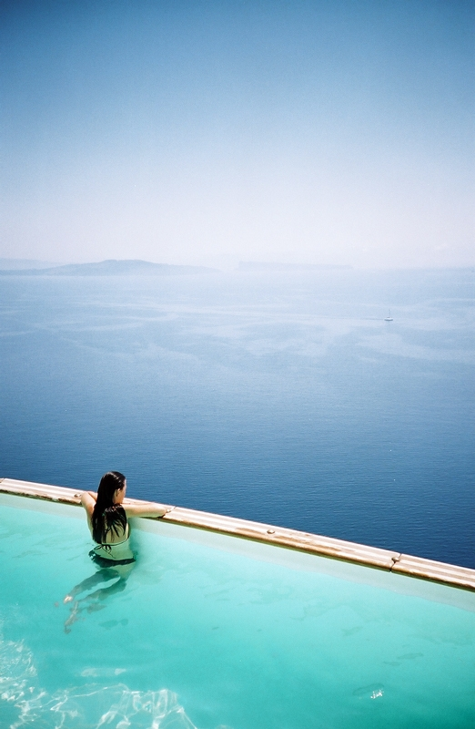 Woman is watching the amazing sea view from the pool of the luxury Nostos Apartments in Oia Santorini