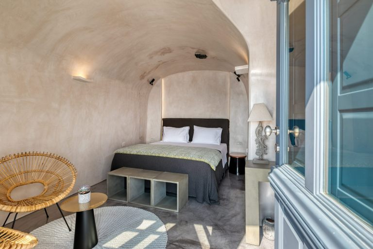 The comfortable double bed inside the bedroom of Nostos Apartments in Oia Santorini